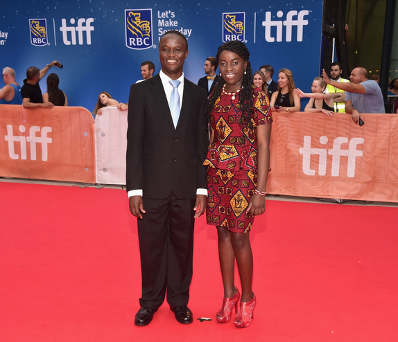 "Chess Coach and Director of Sports Outreach in Uganda, Robert Katende (L) and Ugandan national chess champion Phiona Mutesi arrive at the world premiere of Disney's ""Queen of Katwe"" at Roy Thompson Hall"